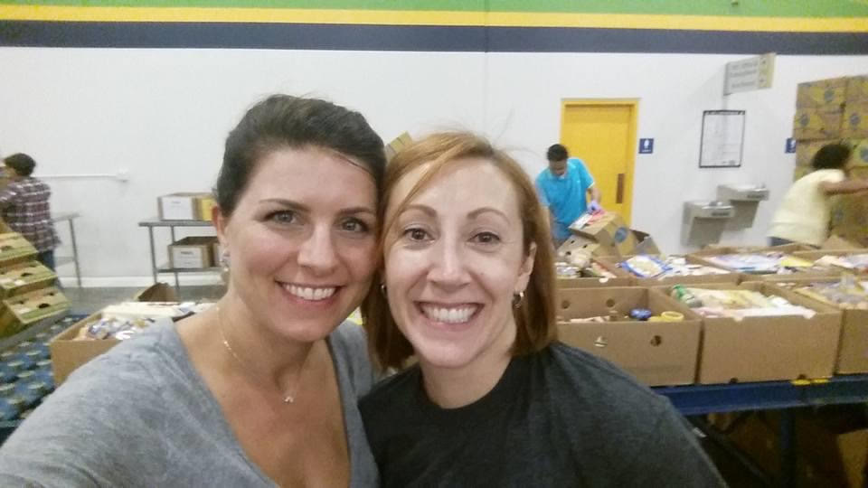 Lauren Fernandez 05JD/MBA, left, and fellow alum Valerie Henderson 06MBA share a smile as they volunteer at the Atlanta Community Food Bank.