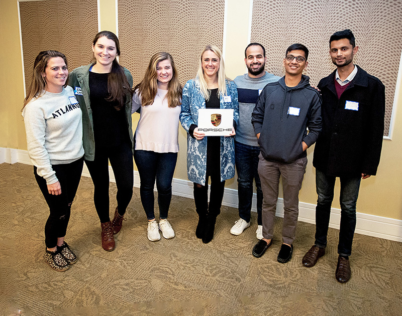 Goizueta Gold first-place winners are, from left, Alexa Newfield, Claire Long (mentor), Jordyn Hodge, Emma Sveen, Mustapha Sakr, Naveen Srikakulam, and Steven Saldanha. Photo taken last fall during Team Reveal, where students learned of project assignments.