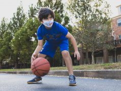 A kid plays basketball at summer camp