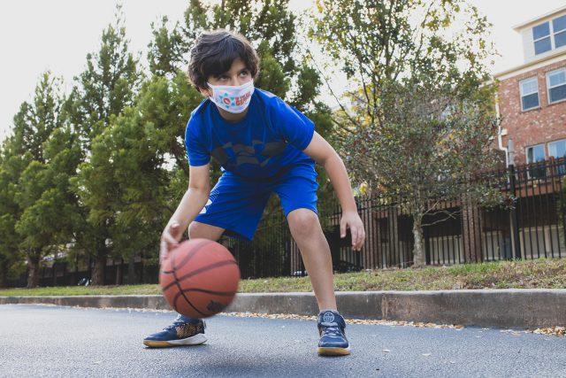 A kid plays basketball at summer camp