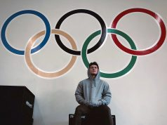 Matthew Jones sits in front of olympic rings