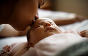 A mother kisses her baby